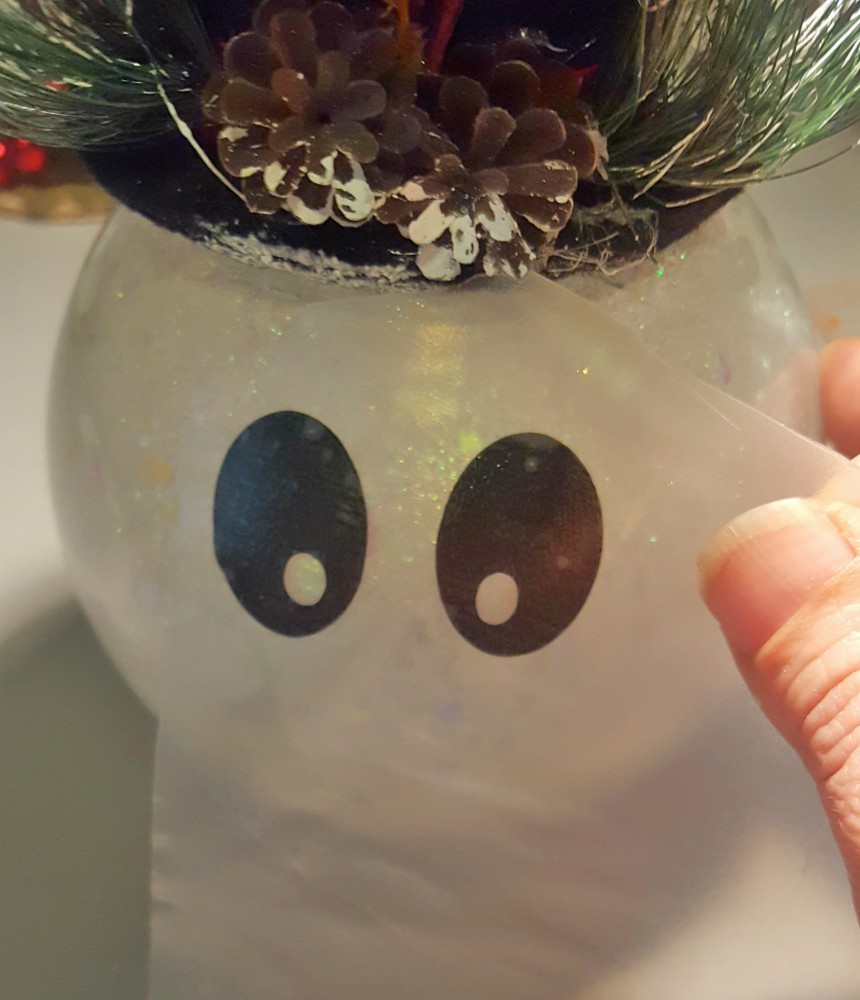 applying vinyl eyes to glass snowman